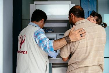 Mercy Corps team member helping a father (holding his daughter) to use an ATM