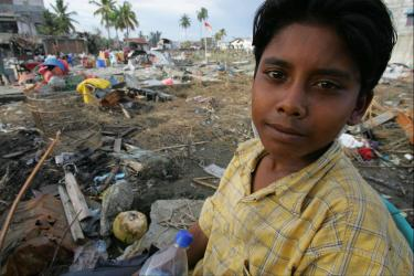 Boy in yellow shirt in front of rubble and debris