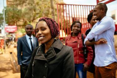 Zipporah smiling with several other people standing in background, also smiling