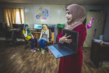 A woman showing a laptop computer to a group