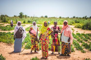 Women in Niger standing in front of a field