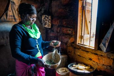 Kenyan woman pouring herbs from her hand into a wooden bowl
