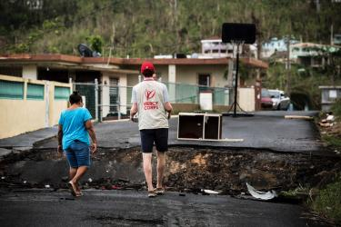 A mercy corps team member carries a tray of food into a village that was hit hard by hurricane maria