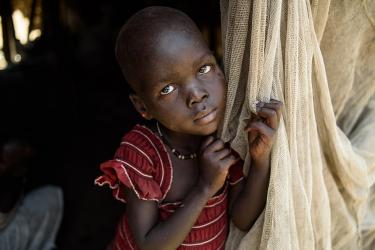 Young south sudanese girl clutching cloth door of tent.