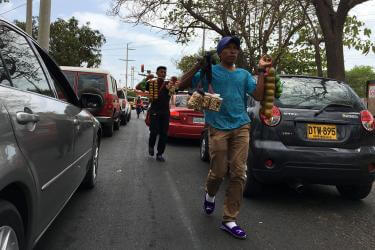 Men walk between cars at a red stoplight offering snacks for sale