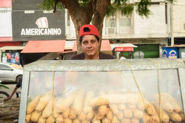 A person in a backwards red cap selling loaves of bread in colombia