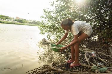 A girl gets water from a stream in colombia