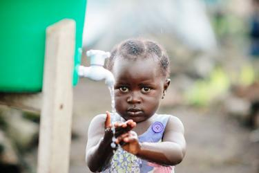 A child washes hands at a hygiene station in a displacement camp on the outskirts of Goma, DRC. In 2015, when this photo was taken, about 5,000 people lived in the camp because of ongoing violence and political instability in eastern Congo. Photo: Corinna Robbins/Mercy Corps