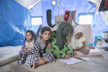 Left to right: Fatima, 5; Siham, 6; Freeal,15; and Amara, 12, draw on the floor inside their family's tent at the Jeddah displacement camp. Temperatures inside the tents can be sweltering as outside temperatures rise above 100 degrees.