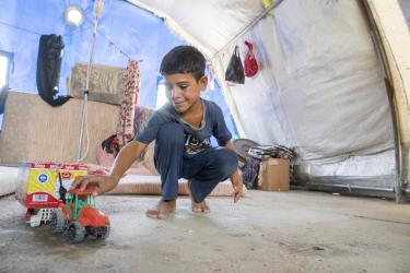 Mohammed, 10, plays with a toy truck that he made inside his family's tent at the Jeddah displacement camp. The toy is a humanitarian aid truck, he says, delivering supplies to the camp.