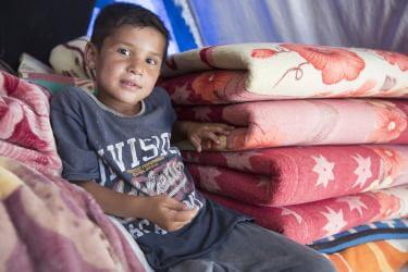 Yaser sits on blankets inside his family's tent at the Jeddah displacement camp. His family has been displaced since the beginning of the conflict when their home was completely destroyed. A kit with household essentials from Mercy Corps ensures his family has a few household items, as they weren't able to bring anything with them when they fled the violence.