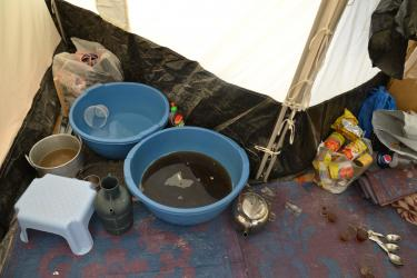 A makeshift kitchen in the back of one family's tent. A dishwashing area, a place to make tea, a trash bag.