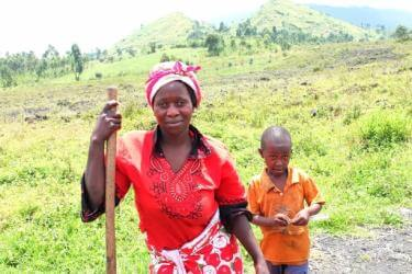 Sifa pictured with her young son, leaning on a farming tool