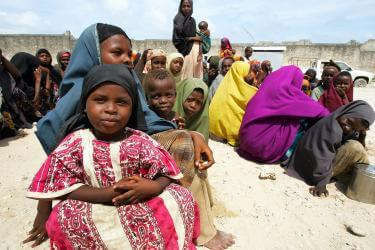 People sitting outside, and a woman holding a young girl in foreground, in somalia