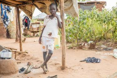 Young south sudanese boy outside a shelter
