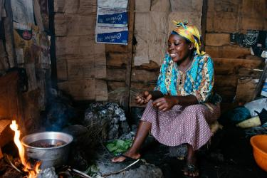 A woman cooks beans over a fire in dr congo