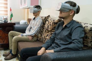 Two young participants in Iraq wear virtual reality goggles which provide visual and audial immersion.