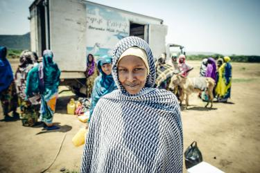 A woman in a headscarf smiles for the camera at a milk sale in ethiopia.