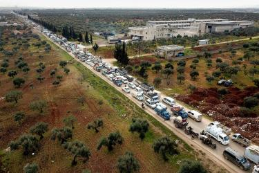Syrians fleeing violence toward camps in northwest syria sit in traffic on a clogged road.