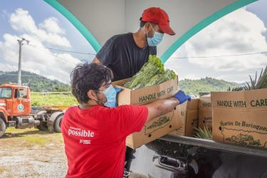 Two mercy corps employees load a truck with food.