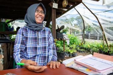 Plant nursery owner smiling at her desk in indonesia