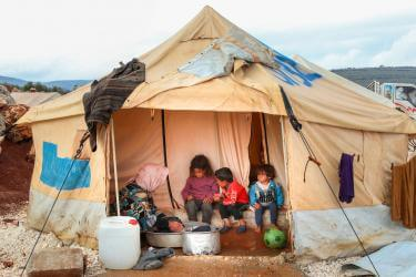 An adult washes clothes, while children sit at the door of their tent in kalli camp.