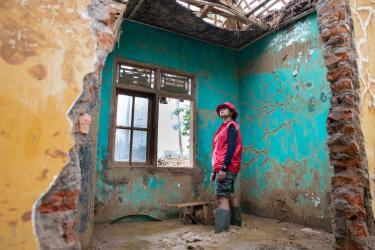 A mercy corps team member surveying the inside of a building damaged by flooding.