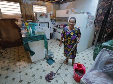 Carmen stands in her kitchen with a mop and bucket