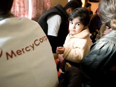 A small child in georgia next to a mercy corps team member