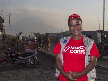 The drc director of communications odette poses for a picture in front of mount nyiragongo volcano.