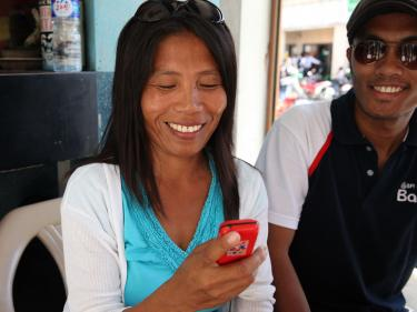 A woman smiles while holding her phone and making a mobile banking transaction.
