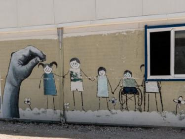 A wall painted with a mural of children holding hands.