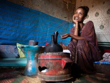An adult sits and waits for coffee to brew inside her home in ethiopia