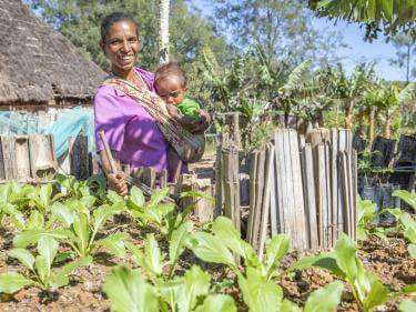 Timor leste woman in vegetable garden with child.
