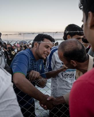 Iraqi civilians displaced after conflict shaking hands over a fence