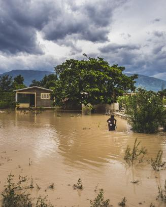 flooded open area in Haiti with a person standing off to the right in the water