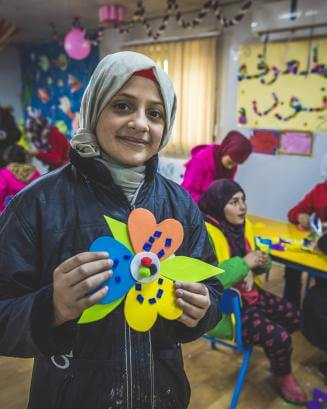 Girl in a classroom in Jordan, holding a craft project and smiling