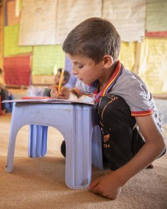 A boy attends class in a tent in an informal settlement outside Mafraq, Jordan